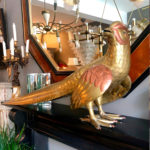 A large and lifesize sculpture of a game bird in brass and copper